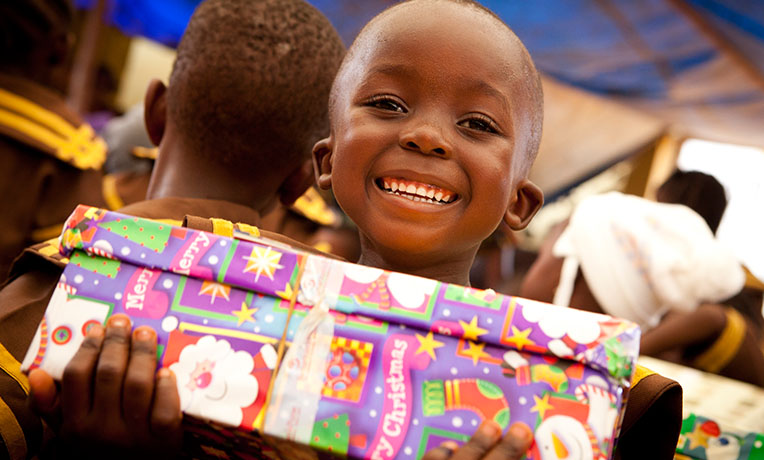 Smiling child with shoebox in Liberia