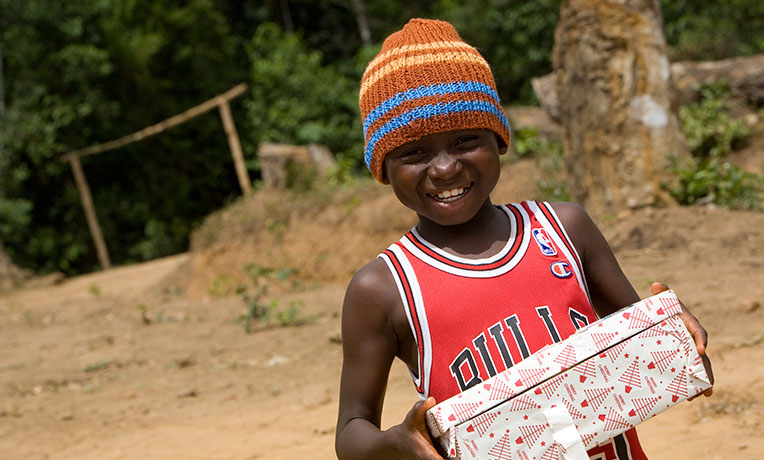 smiling boy with shoebox - wearing a beanie