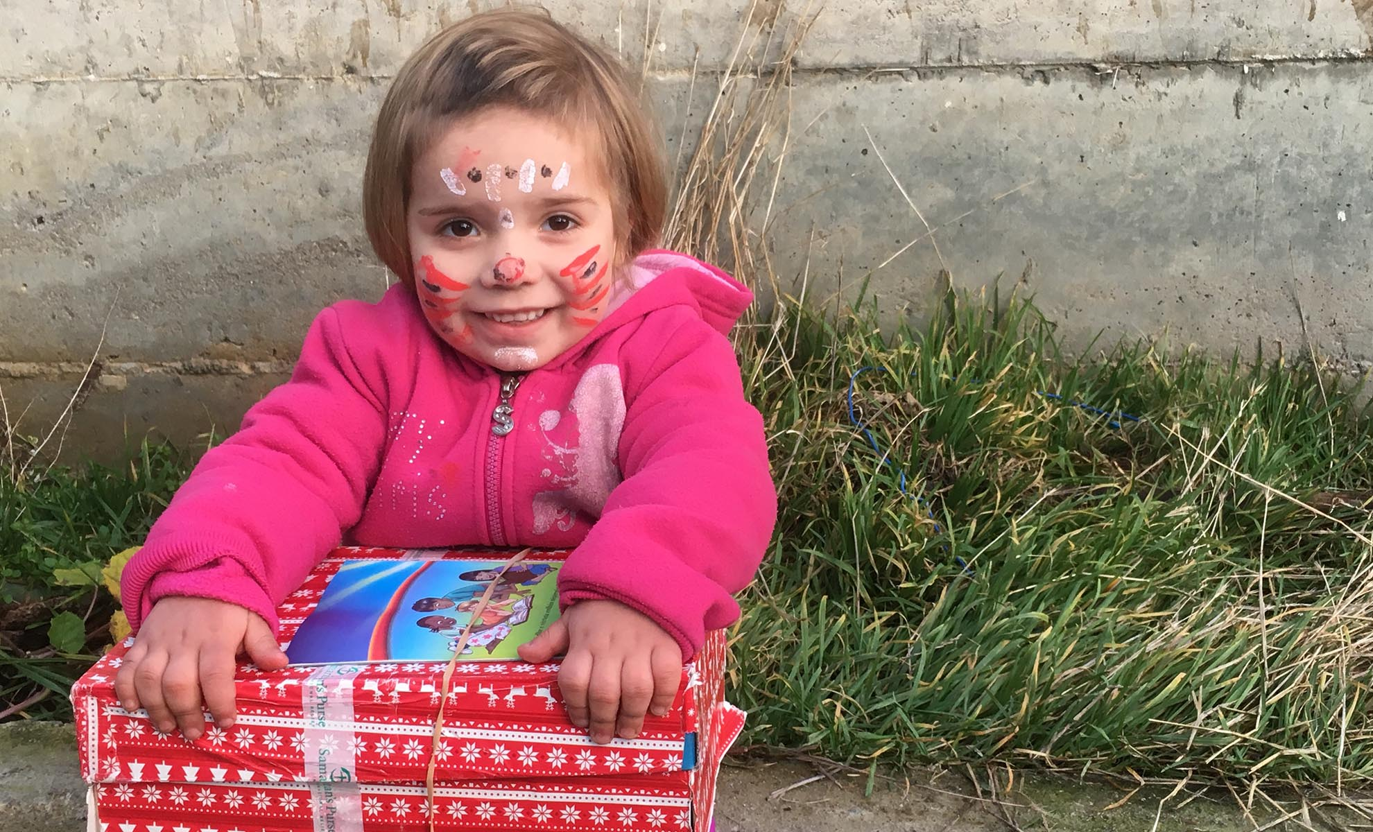 Girl in pink holding shoebox gift in Albania