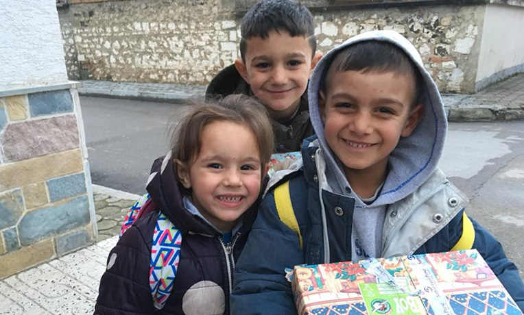 3 children smiling with a shoebox gift