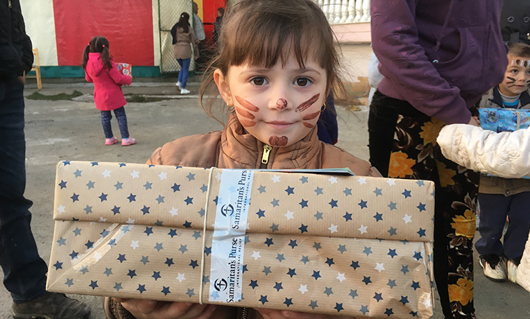 Child with face painted holding a dotty shoebox