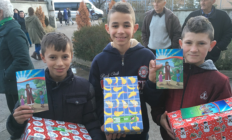 3 smiling boys with shoeboxes and The Greatest Gift leaflet