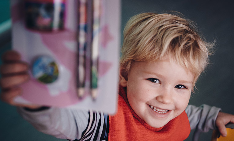 Smiling child shows stationery to camera