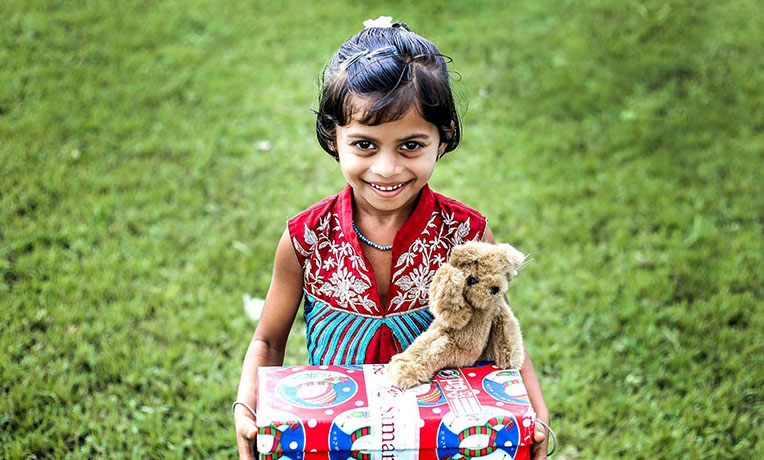 Child with shoebox and teddy