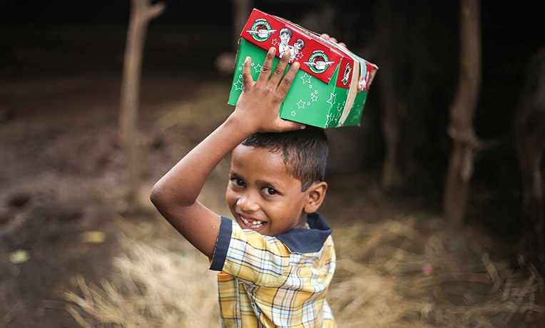 Boy holding shoebox on head