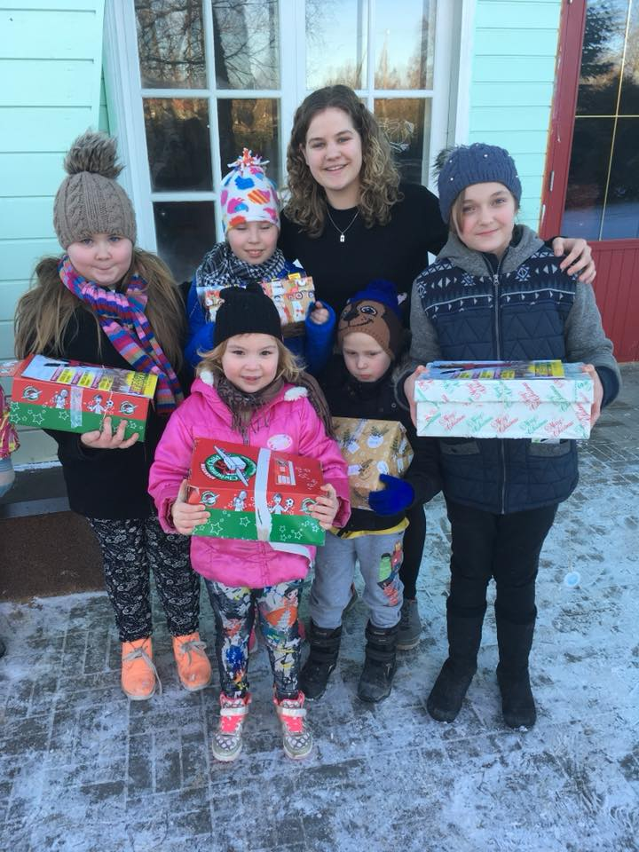 Zoe with a group of children from camp with their shoebox gifts