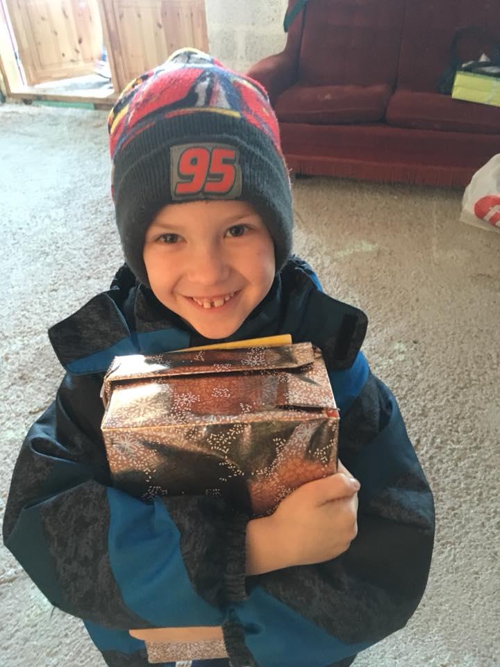Child hugs shoebox gift