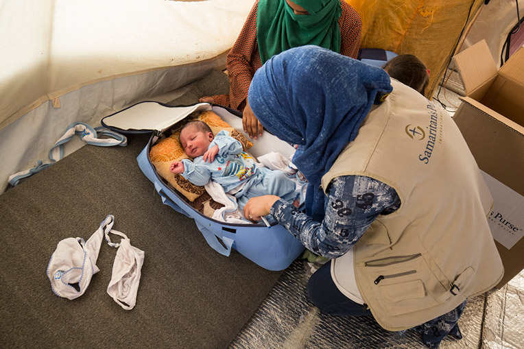 A Samaritan's Purse health worker helps Asim get settled in the bassinet they received.