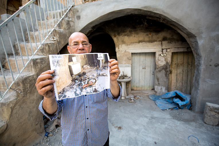 Yohannan displays a photo of what his home looked like when he first returned after Bahzani was liberated from ISIS. Samaritan's Purse is repairing his home.