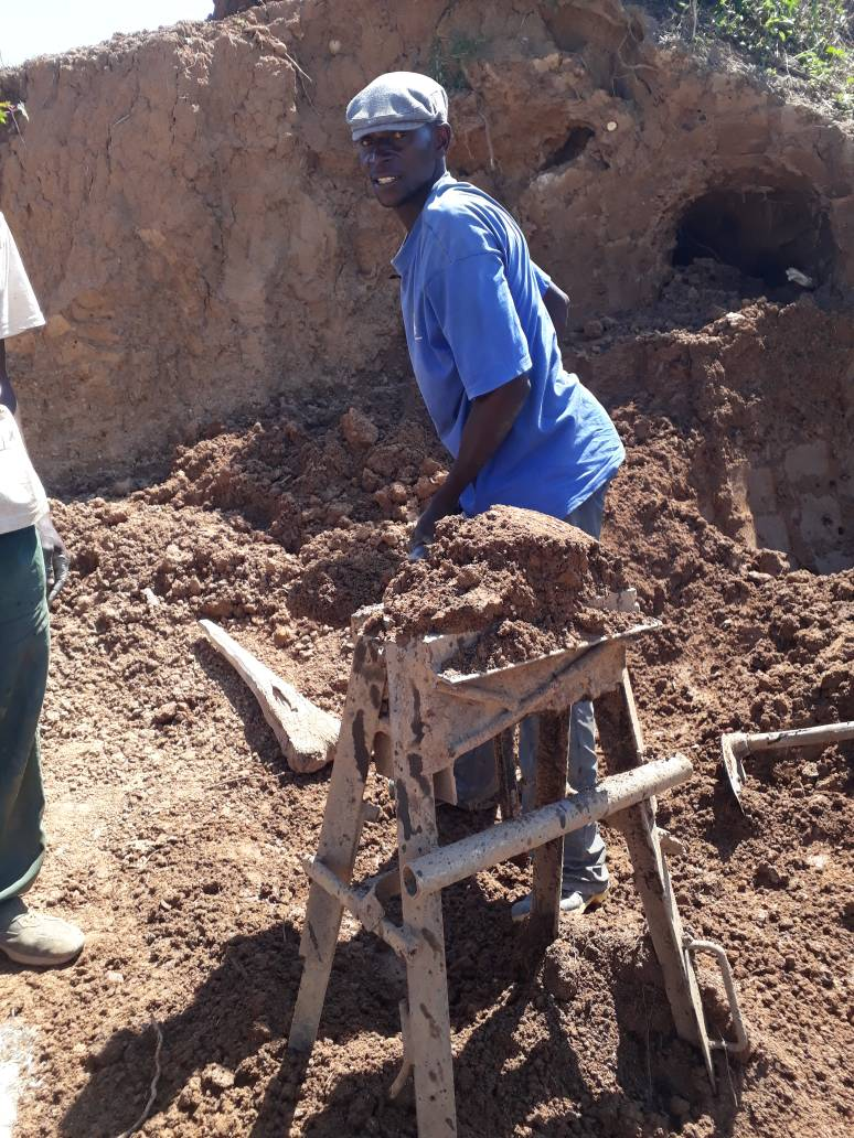 Rev. Kantumoya of Calvary Full Gospel Church prepares clay from an ant hill to be put into the brick molds