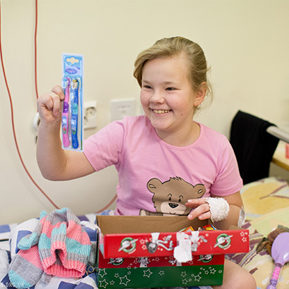 Girl in hospital with shoebox gift