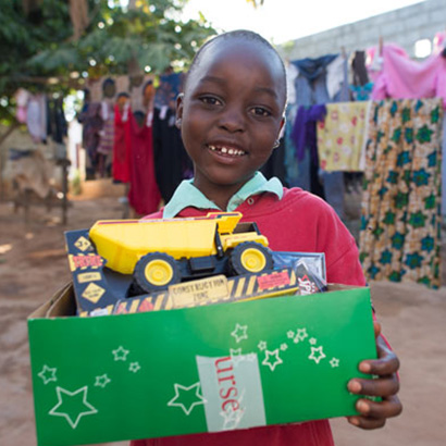Boy with toy truck and shoebox gift
