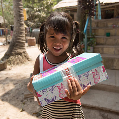 Smiling girl holding butterfly shoebox