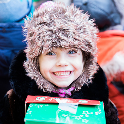 Girl with fluffy hat and shoebox gift