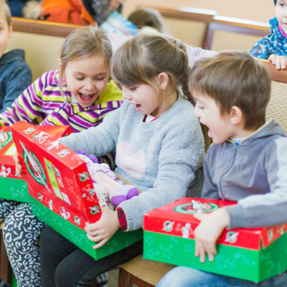 Group of children looking at shoebox gifts in Moldova