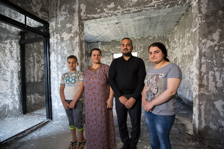 Diana (second from the left) and her three children stand in their home, which was burned by ISIS. Atheer, the family's eldest son , stands to the right of his mother.