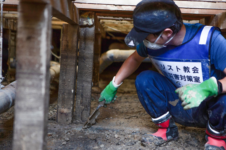 Volunteers are helping clear mud from floor beams in a flood-stricken town in Southern Japan.
