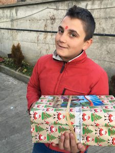 Boy smiling with wrapped shoebox gift