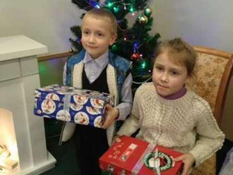Children in front of Christmas tree, holding shoebox gifts