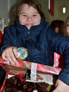 Child grinning with shoebox