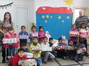 Group of children with shoebox gifts in front of Nativity scene