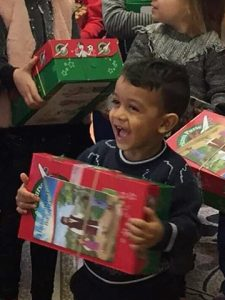 Young boy laughing with shoebox gift