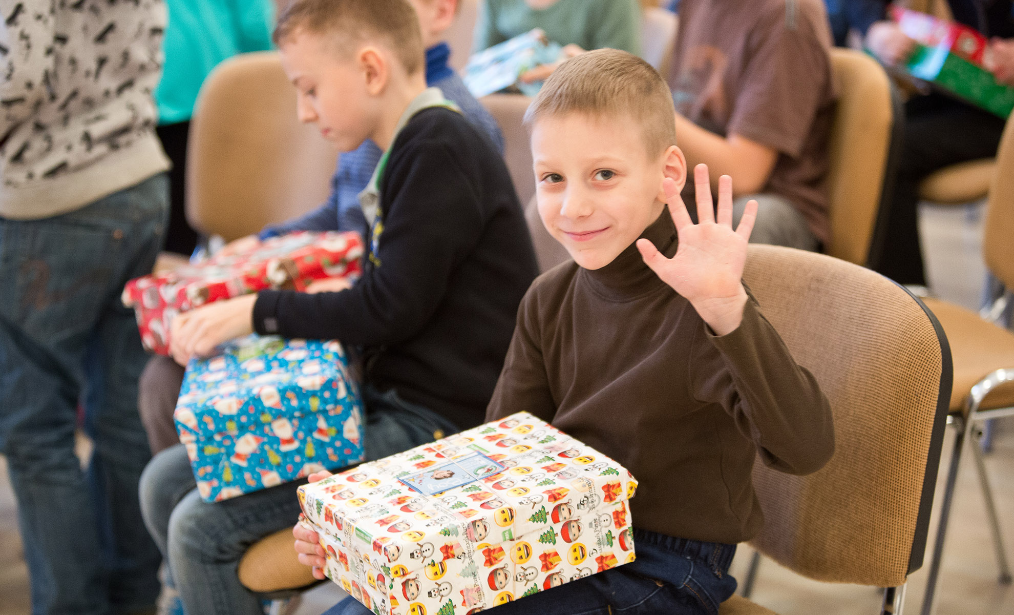 Boy waving with shoebox gift