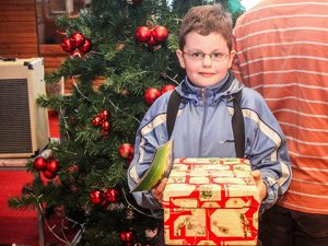 Boy with shoebox gift in front of Christmas tree