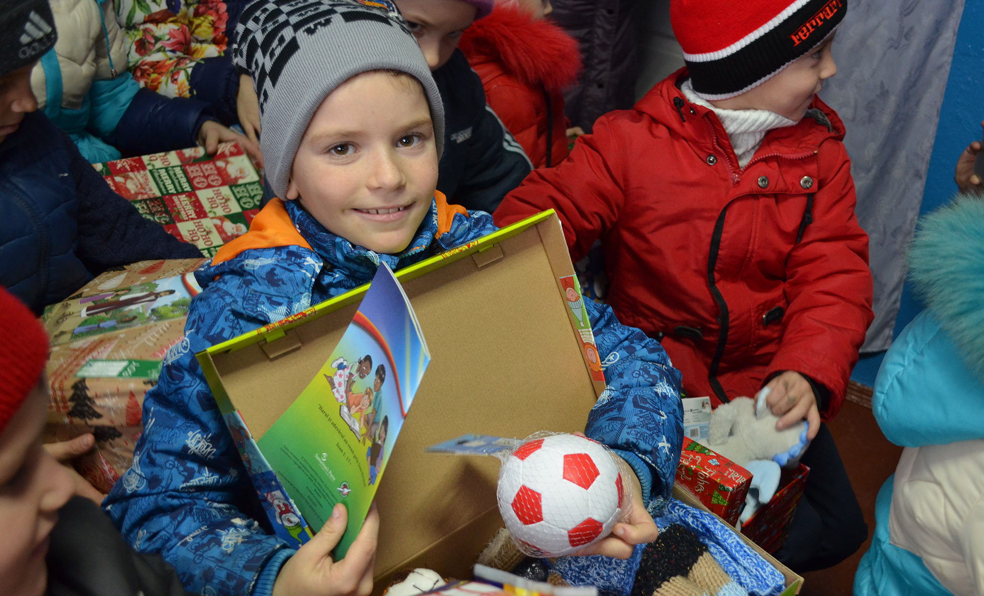 Header image, Boy holding shoebox gift with football