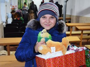 Child with shoebox gift and cuddly toy