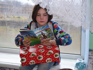 Girl reading The Greatest Gift booklet