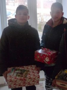 Two boys with shoebox gifts say thank you