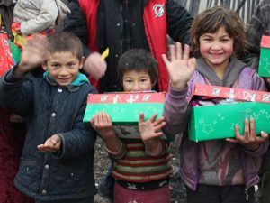 Boys waving with shoebox gifts