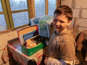 Boy smiles alongside open shoebox gift