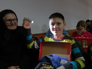 Boy plays with new torch from his shoebox gift