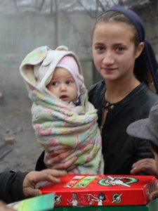 Teen and baby with shoebox gift