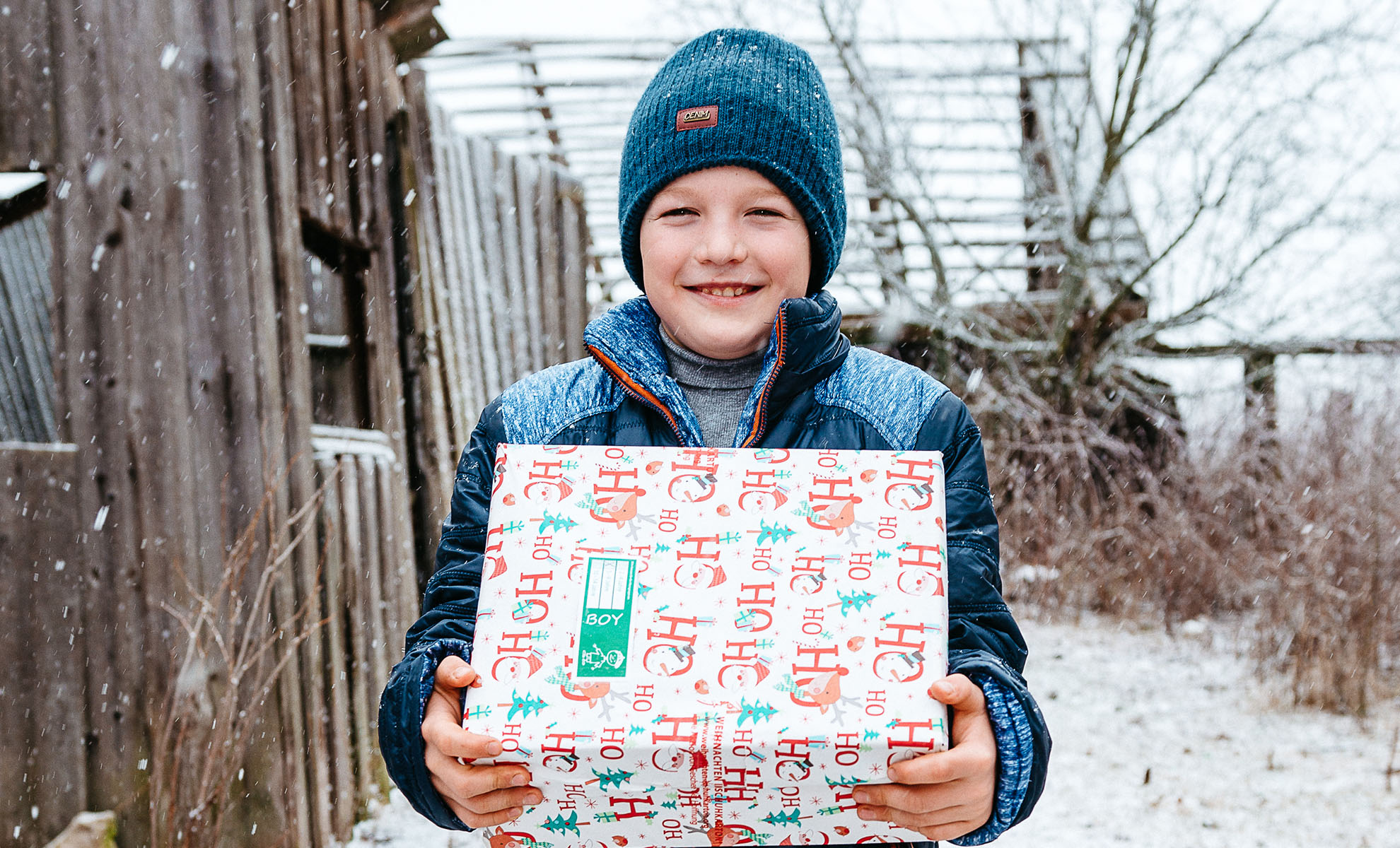 Boy in the snow, holding shoebox gift
