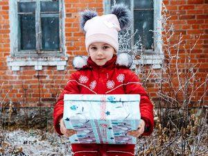Girl outside holding shoebox gift