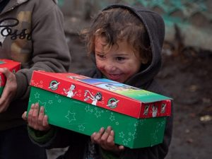 Young boy hugs shoebox gift