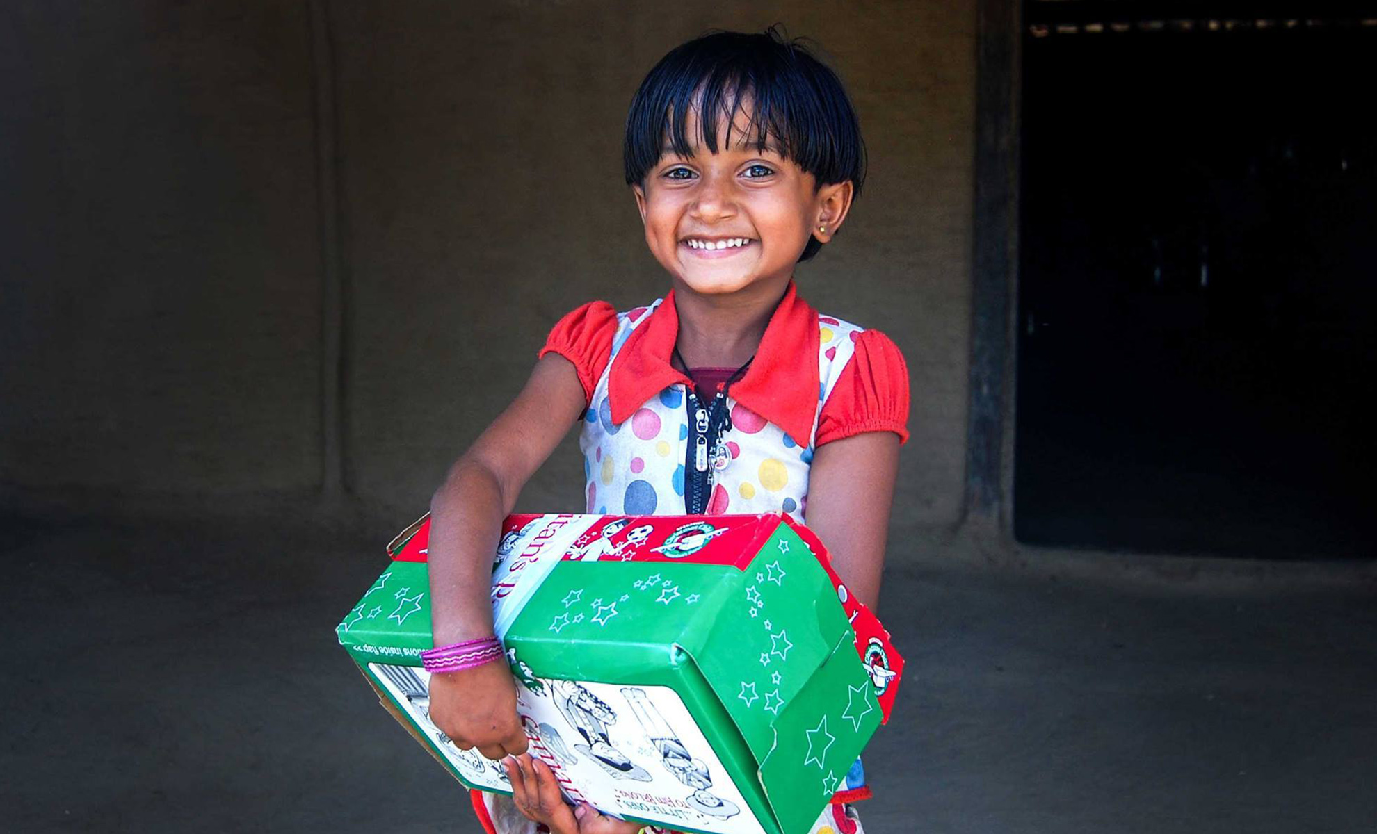 Young girl with shoebox gift smiles