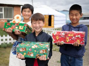 3 boys holding shoebox gifts