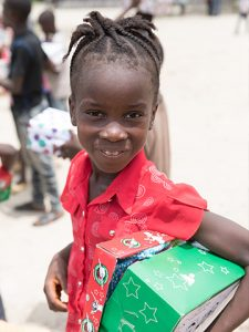 Girl smiles with shoebox tucked under her arm