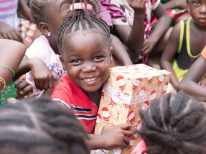 Young girl hugs shoebox and smiles