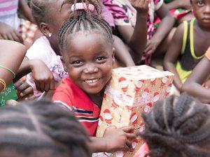Young girl hugs shoebox and smiles