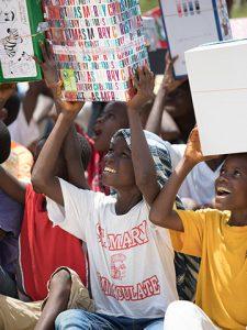 Children hold shoeboxes high