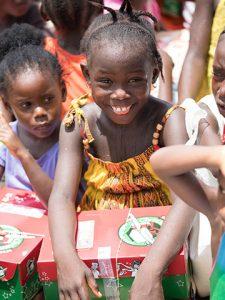 Girl smiles with shoebox