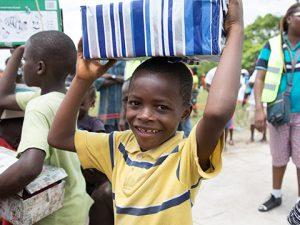 Boy holds stripy shoebox gift on head