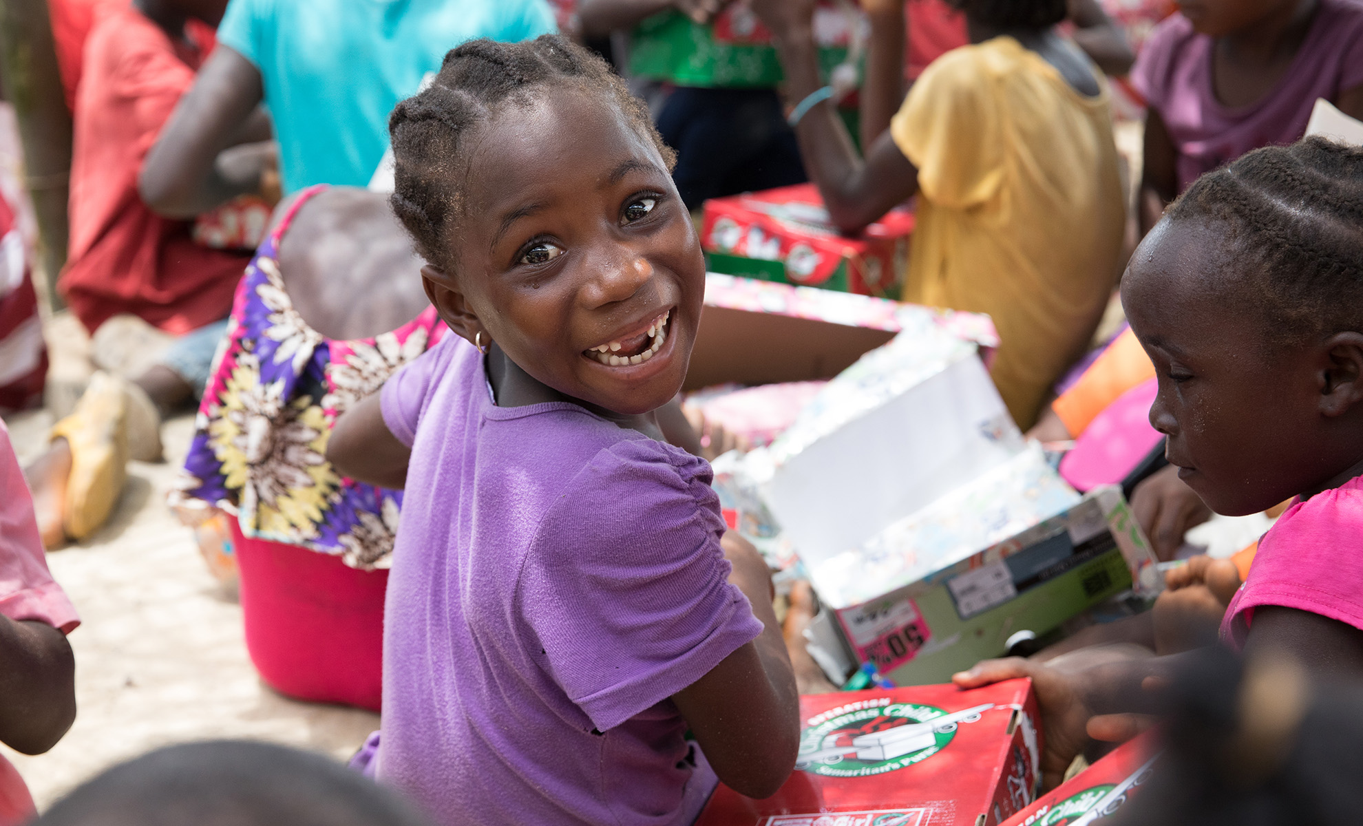 Liberia Header - girl smiles with shoebox