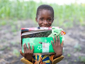 Little girl holding open shoebox gift