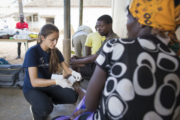 "Jessica Lutz, a Samaritan's Purse nurse, cares for Juliet Luise, a widow. her foot was cut during the cyclone by roof metal. ""We are so grateful for Samaritan's Purse. We thank you so much for coming to visit us and give us medication."""